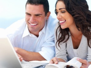 Young smiling couple looking at laptop with book in hand